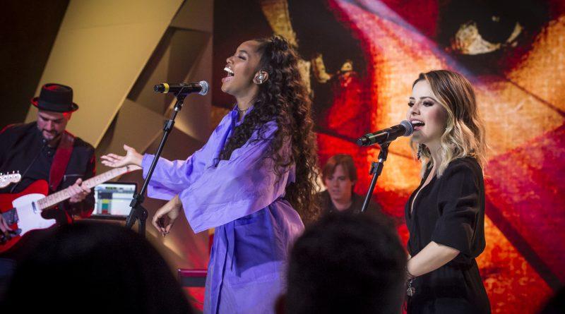 O apresentador Tadeu Schmidt recebe Sandy e Iza no palco do 'Fantástico'. Crédito: Globo/ João Cotta