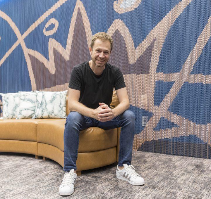 Foto: Globo / Victor Pollak – Tiago Leifert posa no Quarto do Líder do 'BBB 19', em frente ao painel de correntes que decora uma das paredes do ambiente